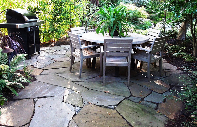 Patio created from large pieces of random-cut flagstone set in sand is stable, yet welcoming.