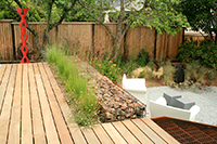 Ipe decking, rock, and steel are simple materials yet accentuate the pop of color of the sculpture.