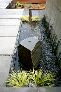The stone was drilled and centered on the steel basin, one of the few symmetrical alignments on the job. The rill makes a right hand turn as it stretches towards the spillway on the other side of the steel wall.