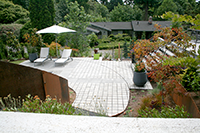 Eco-Prioria pavers were used to satisfy Mercer Island permeable surface requirements. Pavers were cut by hand to accommodate the curved steel edging line that is set into the paver patio grid. The steel edge line visually connects the steel panels in the landscape bed. Furniture-DWR, containers-Ragen & Associates.