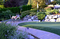A putting green with sitting area by Nyce Gardens