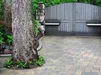 New owner-designed entry gate, and paved driveway, with careful consideration of existing tree